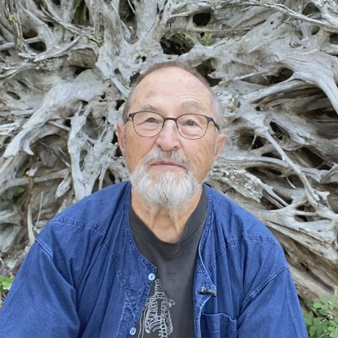 Poet Fred Wah in front of a Cedar Root at Kootenay Lake, BC, Canada.
