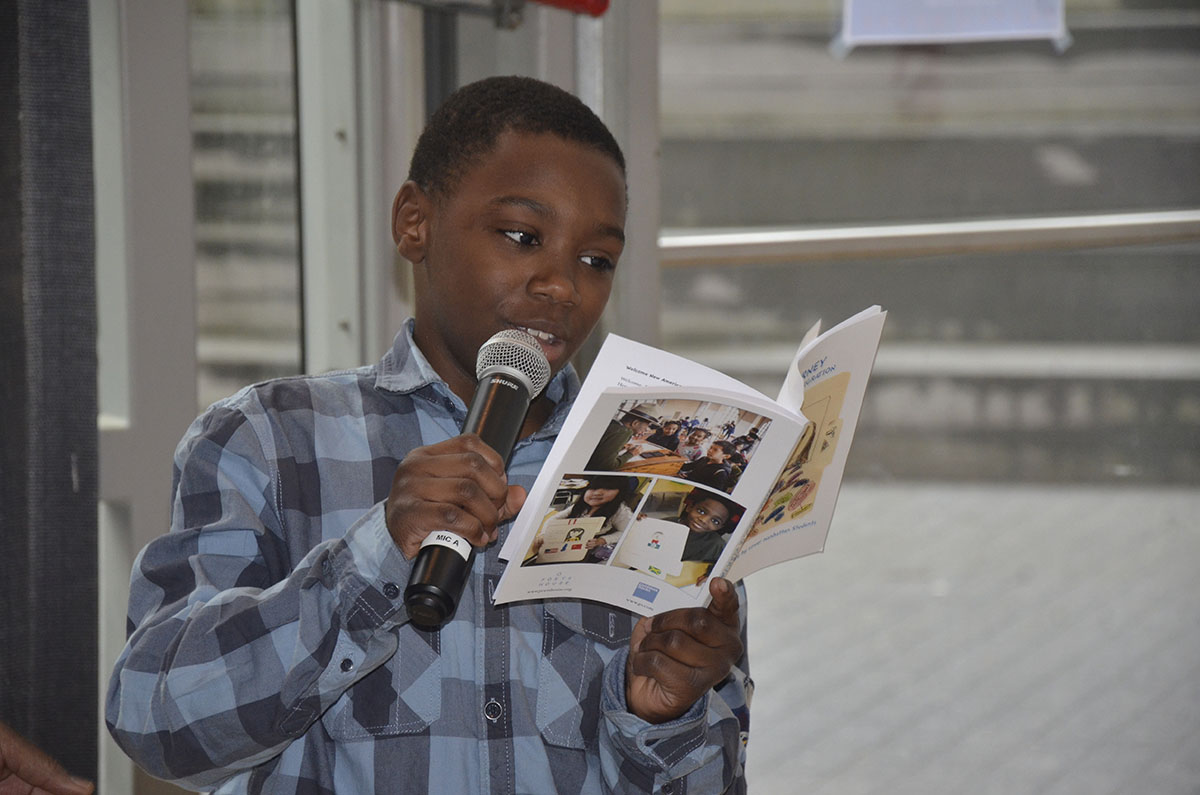 Boy with microphone reading a poem